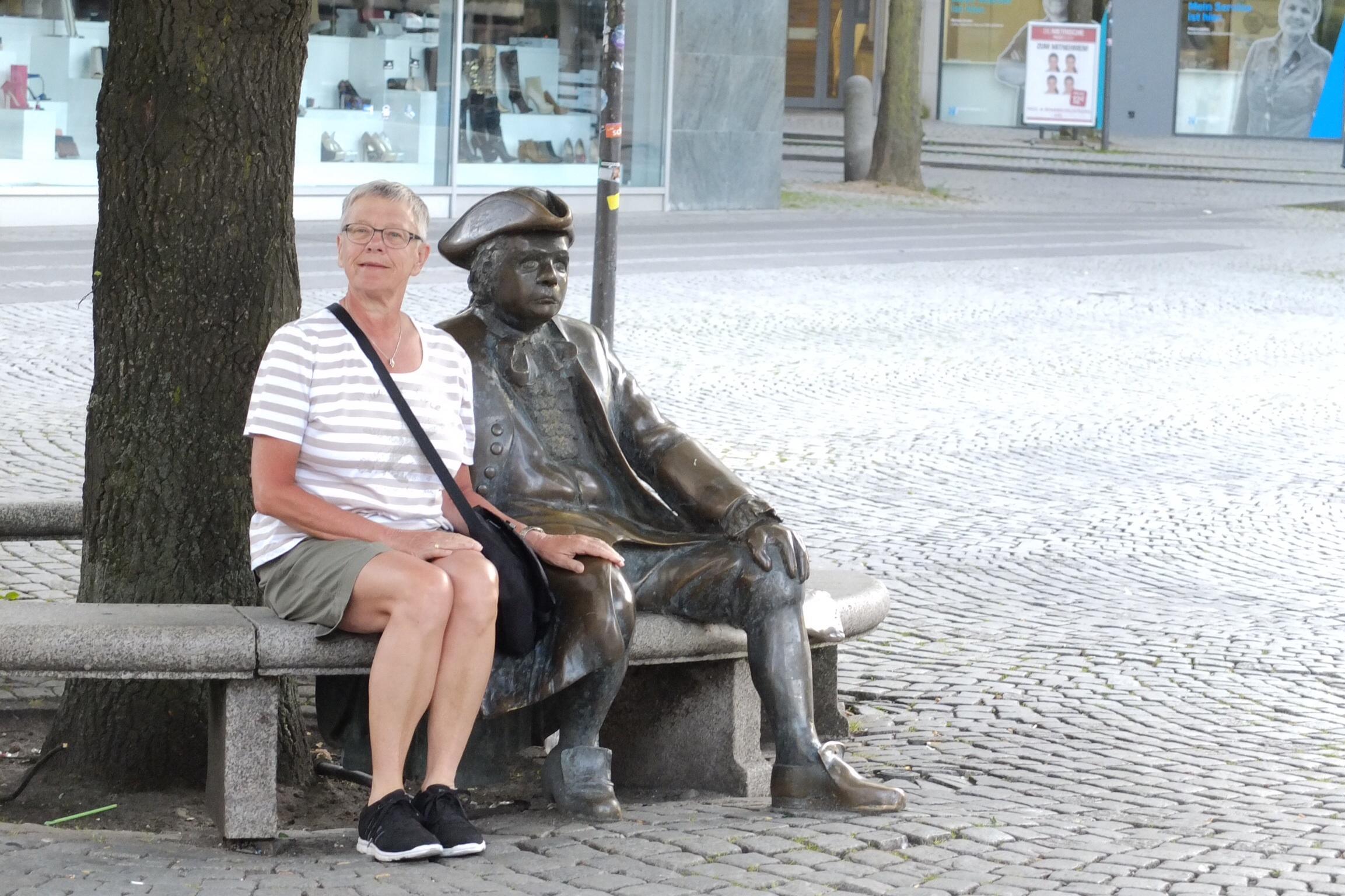 På en bænk på et af Kiels torve fik Lene selskab af en broncekold mand.